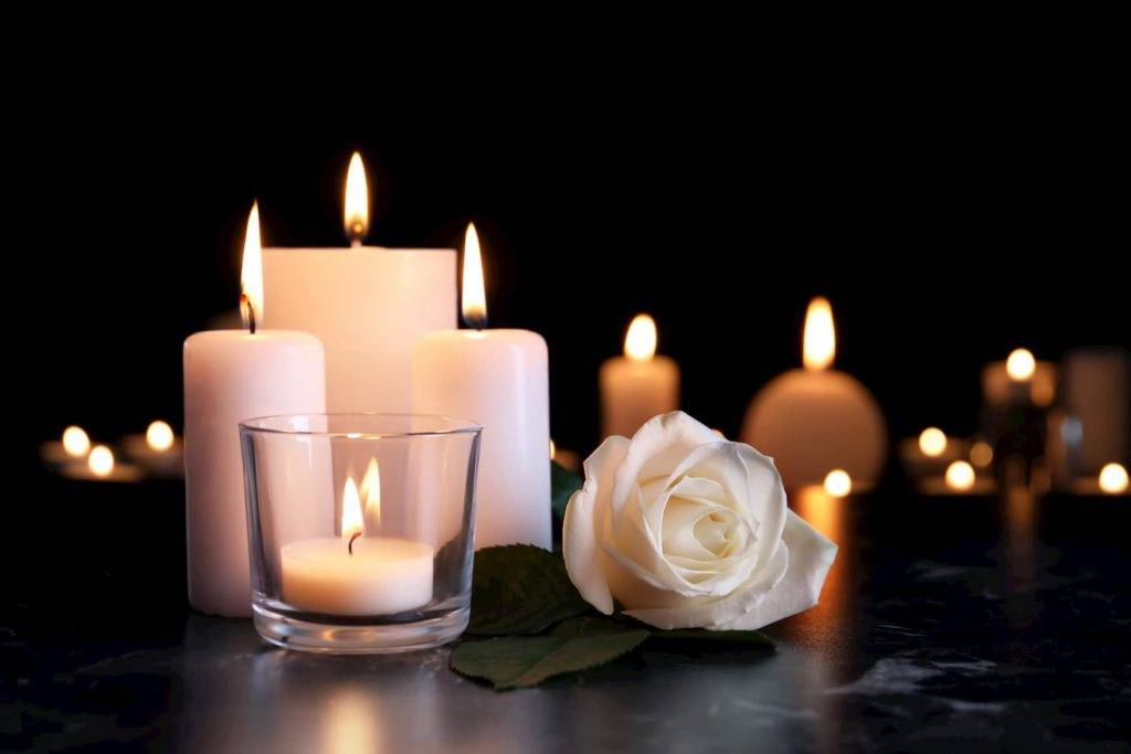 White candles and rose on black marble surface