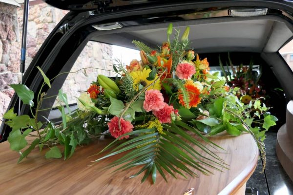 Flowers on top of coffin in back of hearse